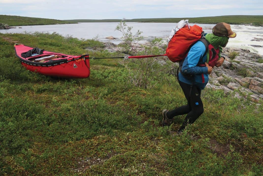 Frank Wolf towing his canoe behind him on a portage