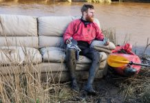 Beau Miles sitting on a couch next to his kayak and his kayak gear