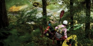 3 kayaker's dragging their boats through a forest with their kayaks and kayak paddles looking at whitewater