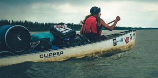 woman paddling a canoe loaded with camping gear