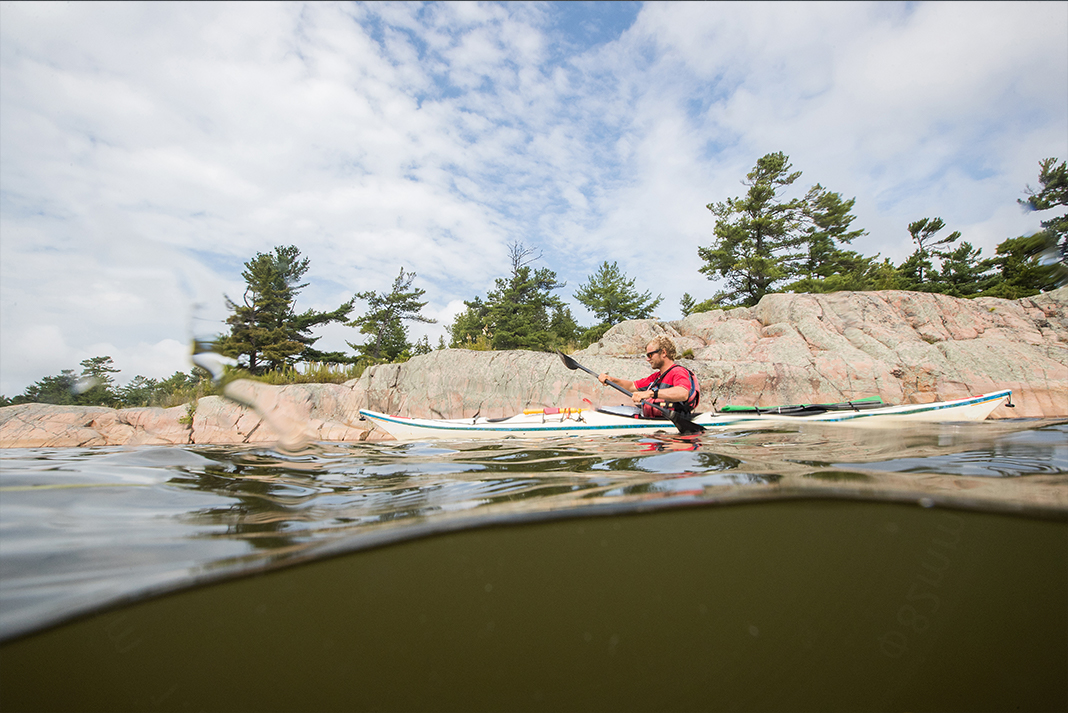 Person kayaking along a rocky shoreline