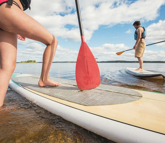 Woman stepping onto inflatable paddleboard. Man in background standing on inflatable paddleboard.