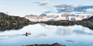 Man paddling on lake with mountains in background