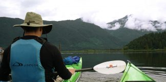 Two green sea kayaks pointed toward cloud-shrouded mountains