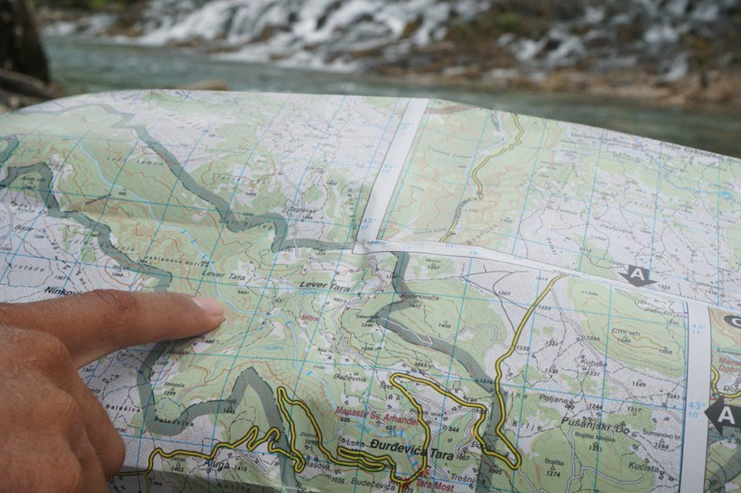 Pointing at a map while planning a kayak expedition