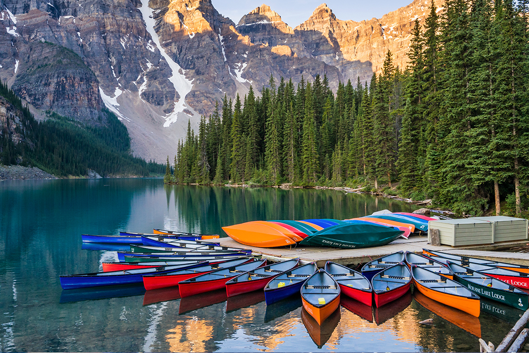 Canoes tied off at dock with mountains in background