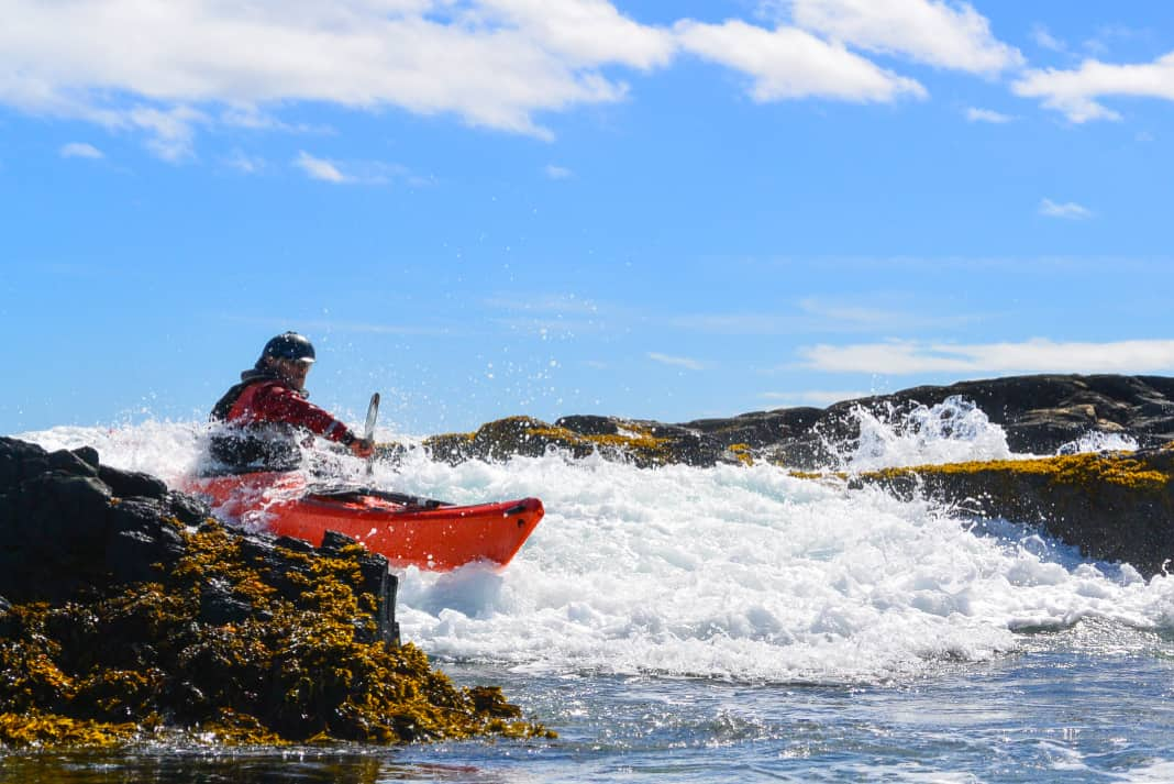 A sea kayaker bounces off a rock in a plastic kayak