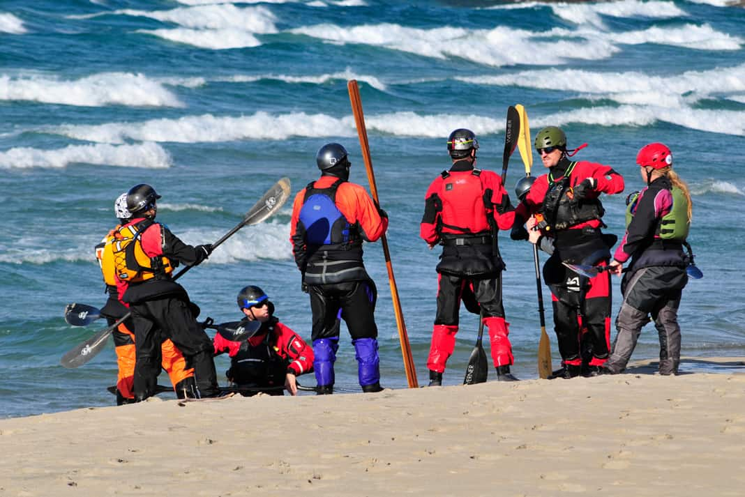 A group of expedition kayakers stand on a beach wearing Gore Tex outdoor gear