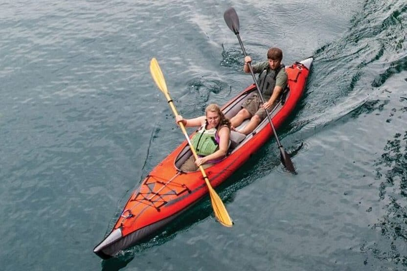 Man and woman paddling in a sit-in tandem kayak