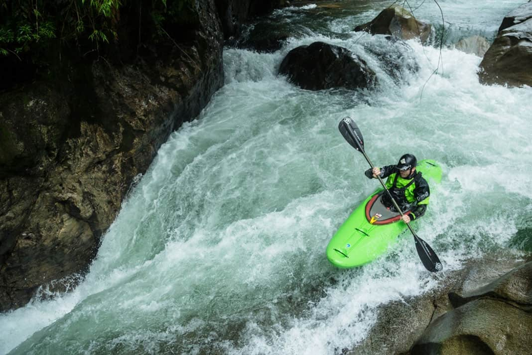 Man in green whitewater kayak going down a raoid