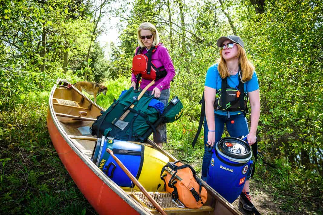 Unloading canoe packs and blue barrels from a canoe