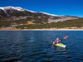 Woman kayaking on lake with mountain in background
