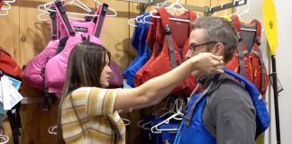Retailer helps a customer fit a life jacket