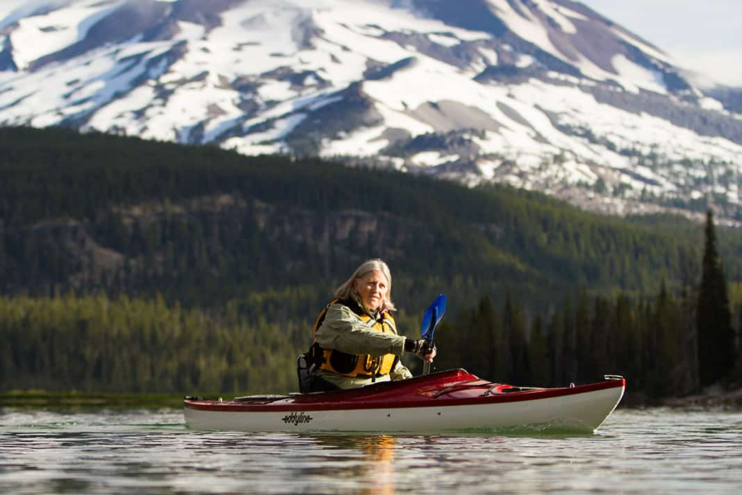 Woman paddling a kayak with mountain in background