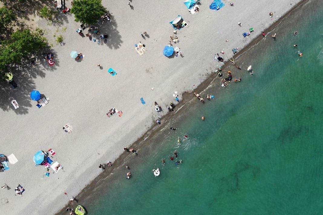 Overhead shot of beach with umbrellas and people walking on it