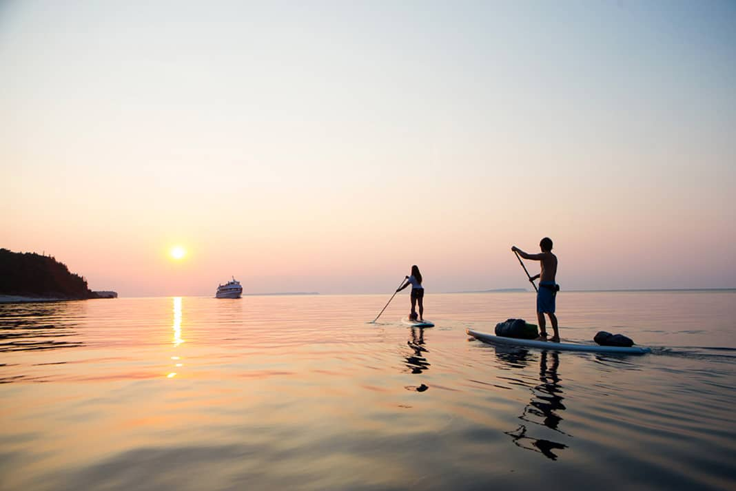Paddleboarders paddling into sunset