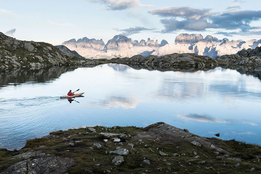Person paddling a kayak across a lake with mountains in background