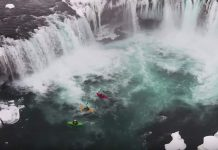 Kayakers at bottom of waterfall