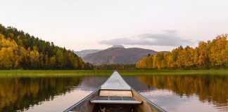 View from the stern of a canoe on a lake, with mountains in background