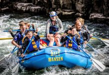 Families in blue raft going down river