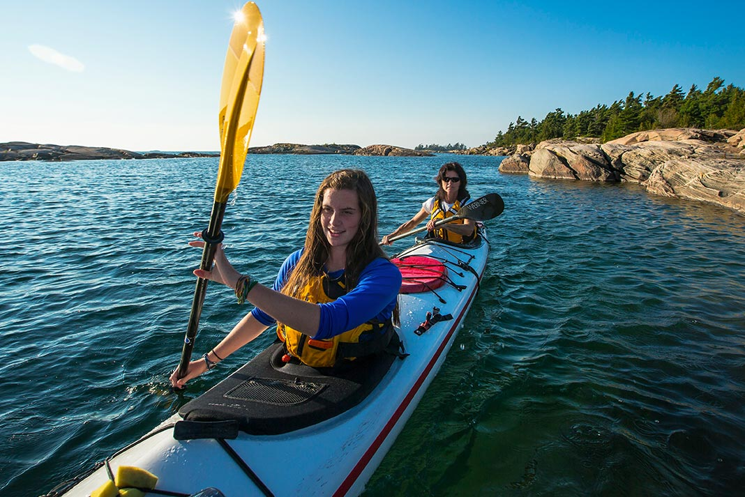 Two women paddling a tandem sea kayak, wearing sprayskirts