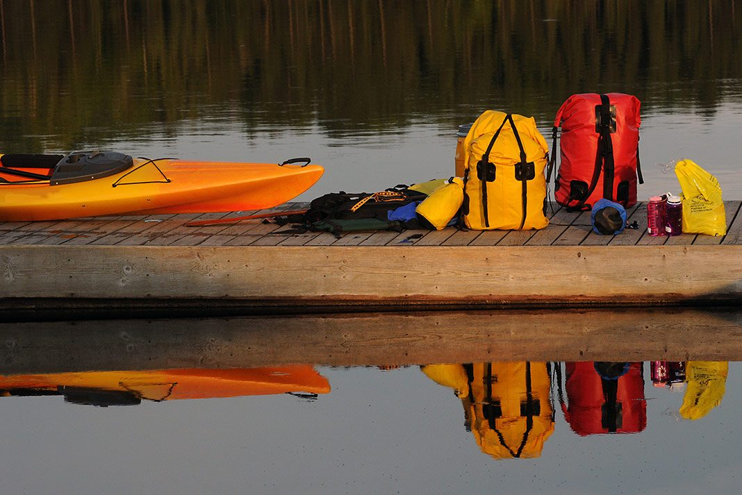 Many drybags sitting on a dock with a kayak in the water