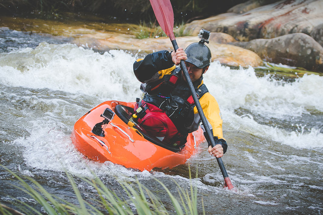Man in orange whitewater kayak with yellow and black drysuit