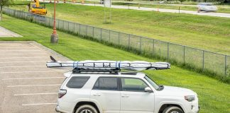 Paddleboard in bag on roof rack of vehicle