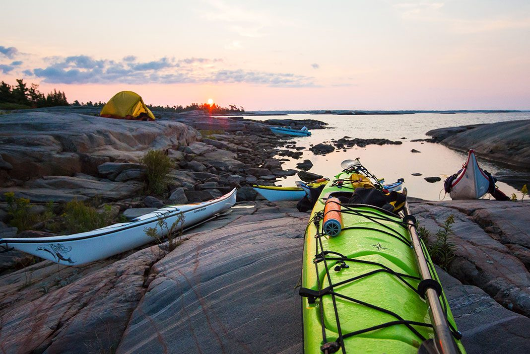 Sea kayaks pulled up on rocks with tents in background