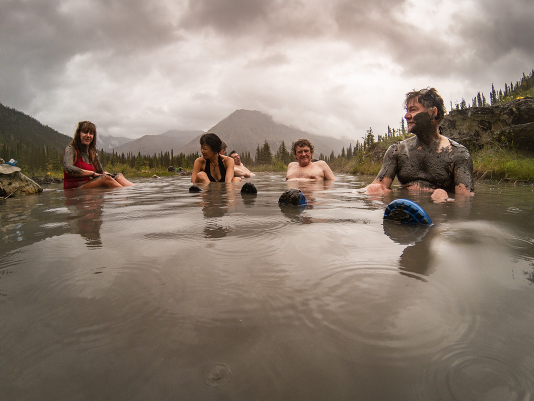 People sitting in a hot spring with mud on them.