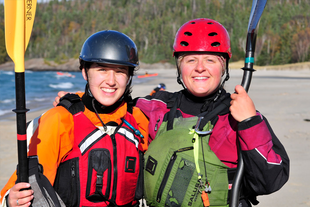 Two women wearing paddling gear, arm in arm