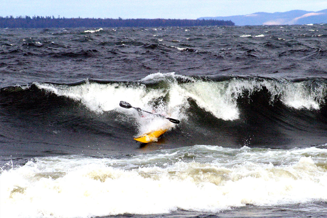 Person in yellow sea kayak coming off a wave