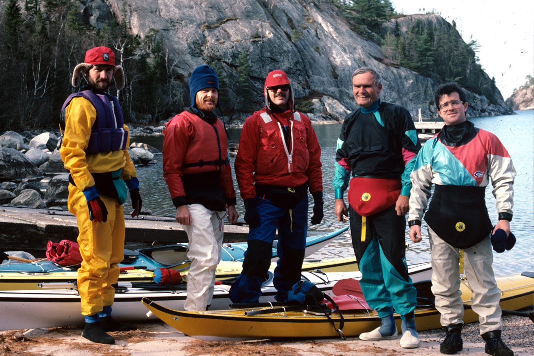 Five men standing beside a lake with sea kayaks at their feet.