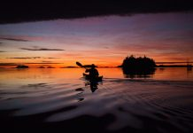 kayaker paddling at sunset