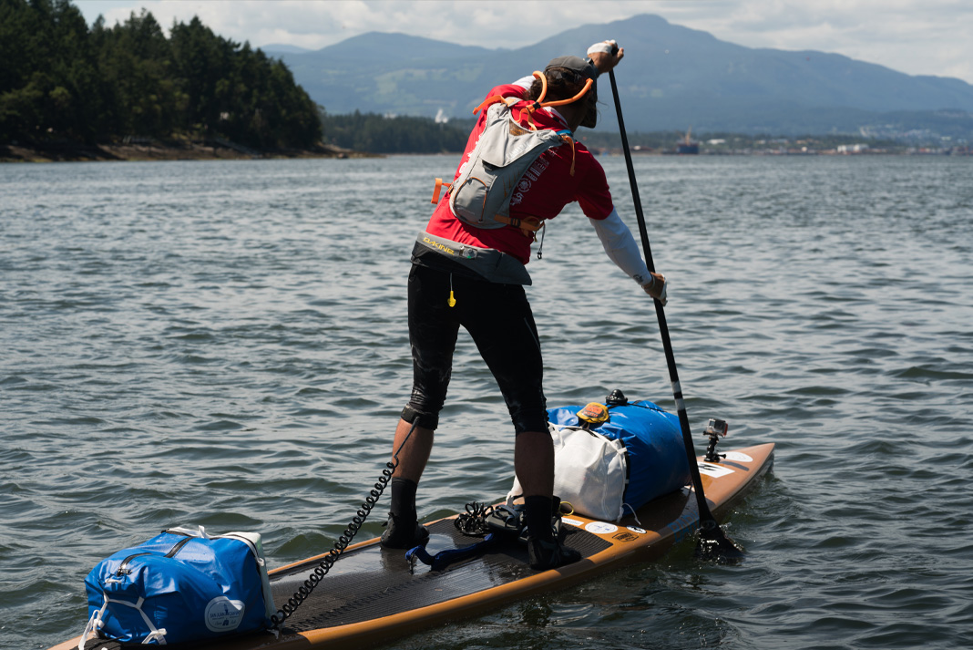 Man on paddleboard with gear strapped down