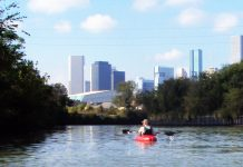 Man kayaking down river toward Houston skyline