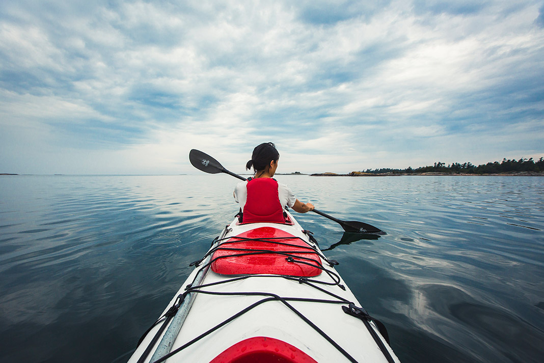Shot from back of a kayak of a woman paddling