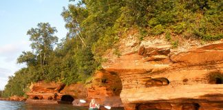 Person kayaking near shore in Apostle Islands