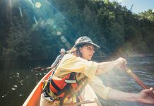 Woman and man wearing hats and long-sleeve shirts in a canoe with sun flare