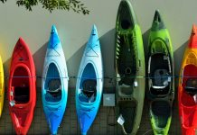 Different sized and colored kayaks leaning up against a wall.