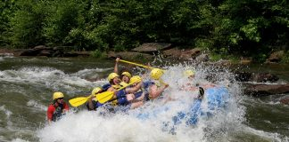 Group of people in a raft going off a wave