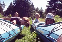 Kids sitting in kayaks on land