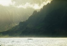 Canoe going past mountainous coast.
