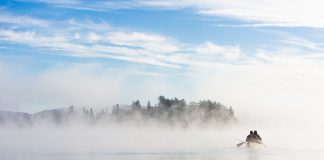 Two people paddling a canoe on a misty lake