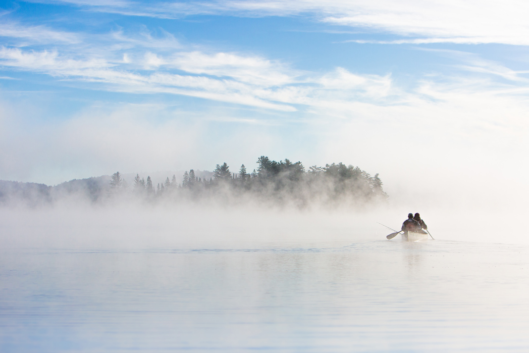 Two figures paddling a canoe on a foggy lake