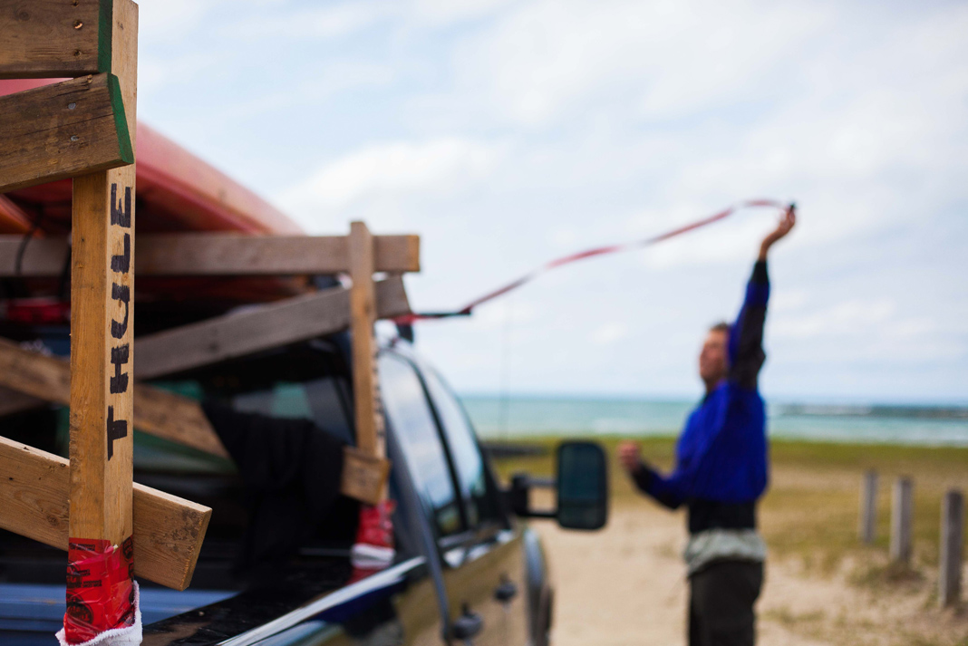 Man strapping down canoe on wooden rack on bed of pickup truck.