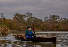 Woman solo paddling canoe with double blade paddle