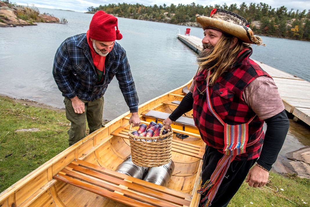Modern day voyageur Mike Ranta [right] helped paddle the first batch of Killarney Cream Ale by Manitoulin Brewing Company from Little Current to the small community of Killarney, on Georgian Bay. This delivery inspired the Current To Killarney race. | Photo: David Jackson