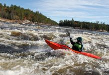Person in red whitewater kayak