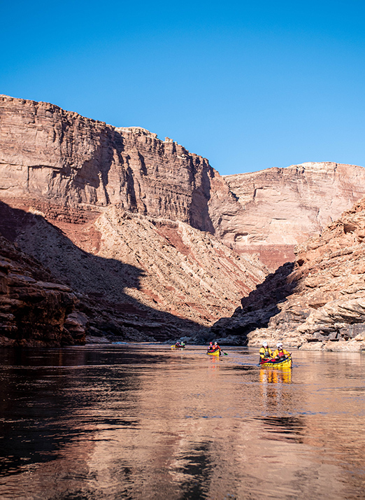 Canoes on river with canyon walls on either side